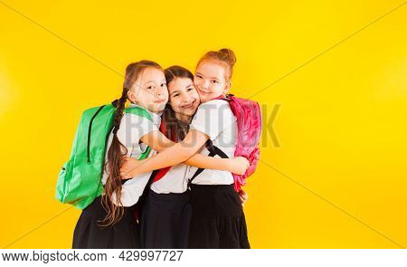 Three Girls Classmates Are Hugging On A Yellow Background