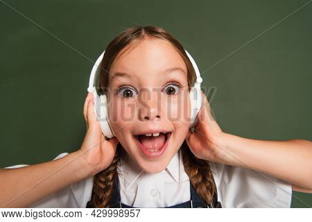 Excited Schoolkid With Open Mouth Touching Headphones While Standing Near Chalkboard