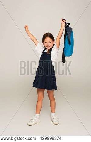 Excited Schoolkid With Blue Backpack Showing Win Gesture On Grey