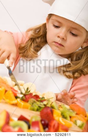 Little Girl Chef With Lots Of Fruits
