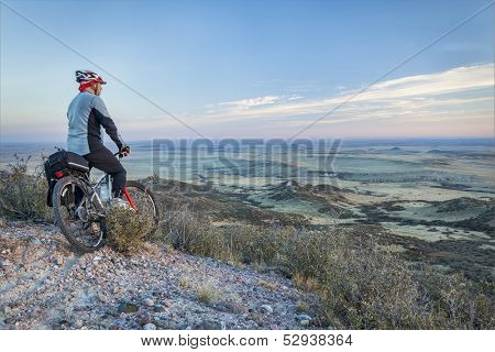 senior male on a mountain bike contemplating a view of rolling prairie at dusk, Soapstone Prairie Natural Area near Fort Collins, Colorado