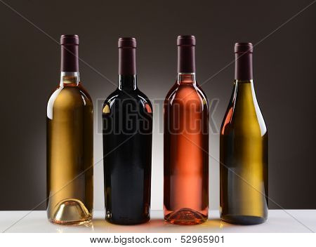 Four Wine Bottles with no labels on a light to dark gray background. Four different wines including: Cabernet Sauvignon, Chardonnay, Sauvignon Blanc, and White Zinfandel.