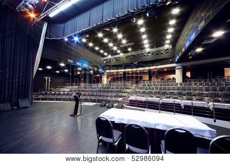 Document stand and table on stage and rows of seats in black hall for business meetings.