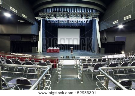 Chairs with handrails and stage with desk in modern hall for business meetings.