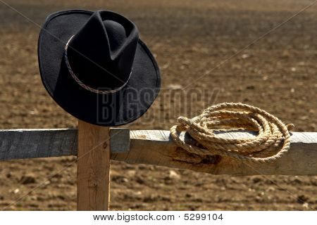 American West Rodeo Cowboy Hat and Rope on Fence