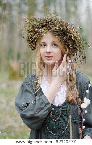 Portrait Of A Girl In A Folk  Medieval Style With A Circlet Of Flowers Touching Her Face