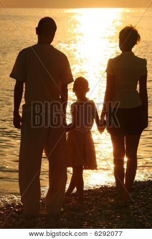 three silhouettes against glossing sea. Parents and daughter.