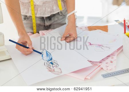 Closeup mid section of a female fashion designer working on her designs in the studio