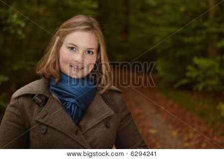 Freindly Young Woman Standing By A Forest Path