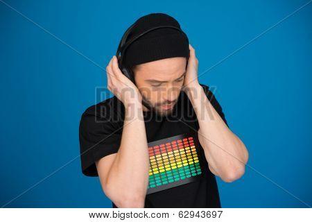 man dj wearing headphones on blue