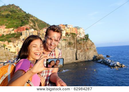 Selfie - couple taking picture in Cinque Terre, Italy with smartphone. Couple taking self portrait photo on holidays travel. Young man and woman backpacking in Manarola, Cinque Terre, Liguria, Italy