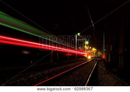 Train tracks with train lights trail going foward poster