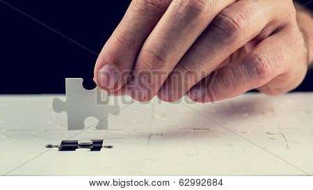 Man Placing The Last Piece In The Jigsaw Puzzle