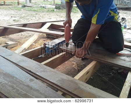 Carpenter drilling a screw into wood