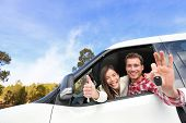 New car - happy couple showing car keys driving having fun on road trip drive in rental car. Happy lifestyle with beautiful young interracial couple outdoors on travel. Man driver and woman passenger. poster