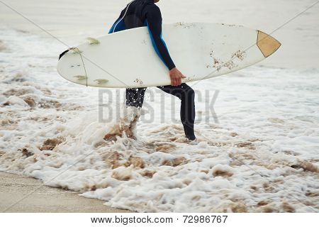 Man surfer with surfboard, surfer man carrying his surfing board, surfer in wetsuit holding a board