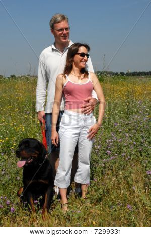 lovers and their rottweiler in a field poster