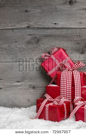 Pile of red Christmas gifts,snow on grey wooden background.