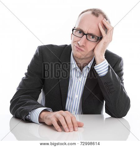 Frustrated businessman wearing glasses sitting at desk with head in hand isolated on white background