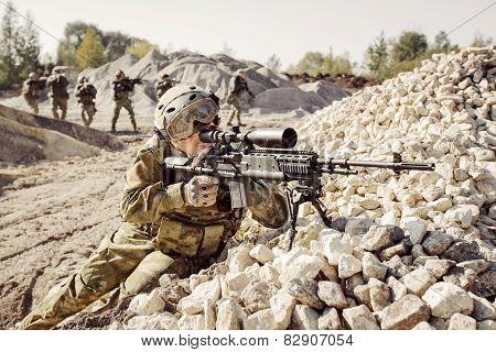 Sniper Covers Offensive Squad Of Soldiers