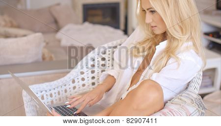Pretty sexy blond woman relaxing in a white wicker chair in her living room working on a laptop computer with a smile  side view