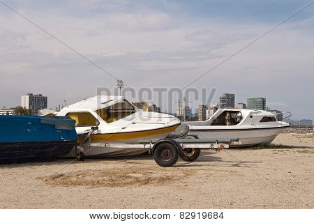 Abandoned rusty boats and trailer on the beach. poster