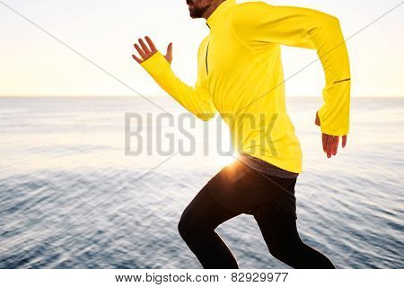 Sport Fitness Runner Running Outside At Sunset At Beach Near Deep Blue Sea.