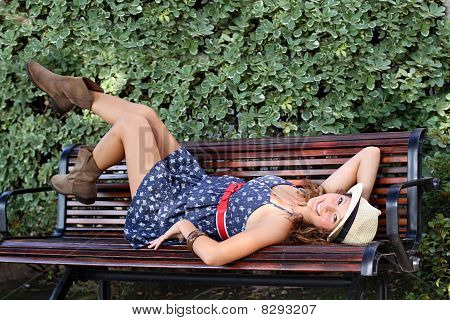 Cute Girl Laying On A Bench