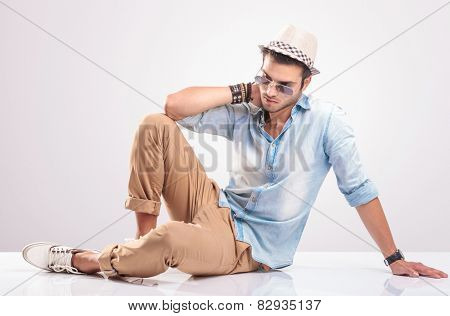 Full body picture of a young casual man lying on the floor, holding his hand to his neck wile looking down.