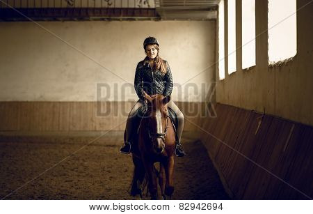Young Woman Jockey Sitting On Brown Horse At Indoor Arena