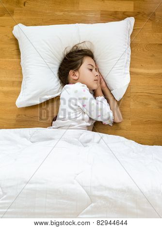 Brunette Little Girl Sleeping On Floor Covered With Blanket