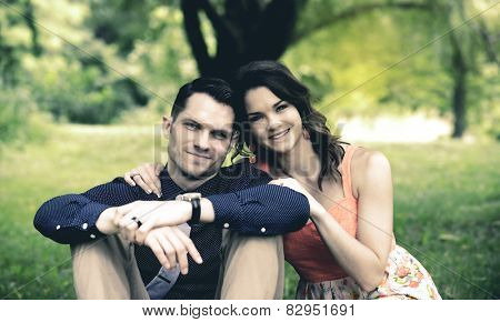 Instagram look of an image showing a happy young couple sitting on the ground in a garden setting after becoming engaged.