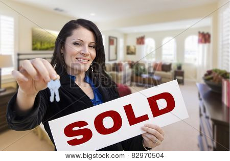 Happy Hispanic Woman with House Keys and Sold Sign in Beautiful Living Room.