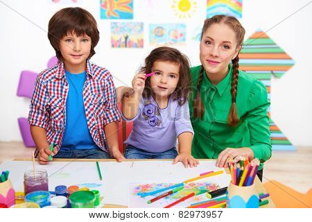 Teacher with children drawing and looking at camera