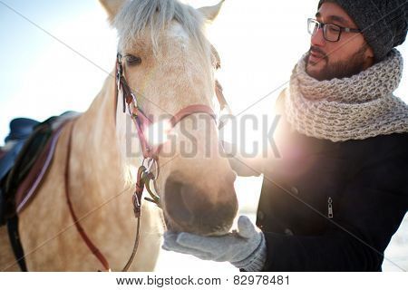 Young man in winterwear and his horse