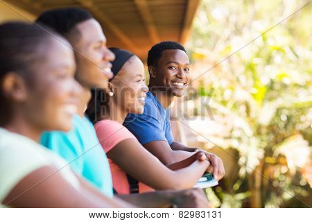cheerful young african college boy with friends on campus