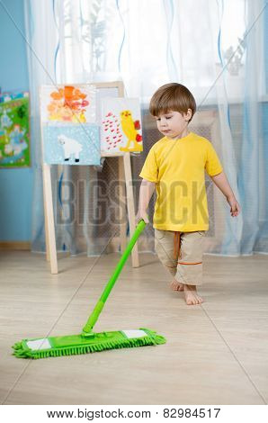 kid boy cleaning room, washing floor with mop. Little home helper. poster
