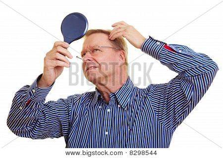 Man Watching His Receding Hair Line In Mirror