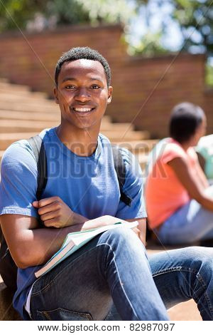 good looking male african college student sitting on steps