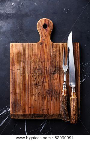 Chopping Cutting Board And Fork And Knife Carving Set On Dark Marble Background