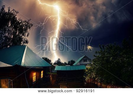 Thunderbolt over the house with dark stormy sky on the background and moon shining through the cloud