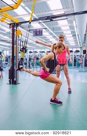 Personal trainer teaching to woman in suspension training