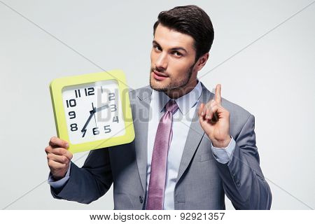 Confident businessman holding clock over gray background and looking at camera