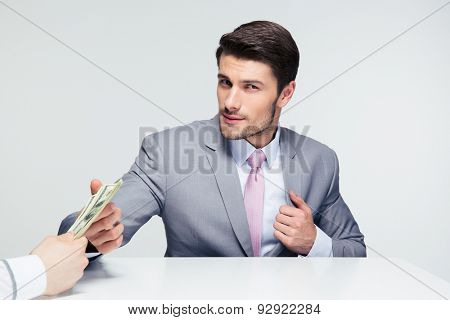 Businessman sitting at the table and taking bribe over gray background. Looking at camera