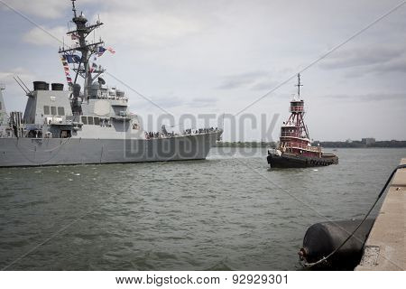 STATEN ISLAND, NY - MAY 20, 2015: USS Stout (DDG 55) is guided into port by a McAllister tugboat at Sullivans Pier in Staten Island after the Parade of Ships at the start of Fleet Week.