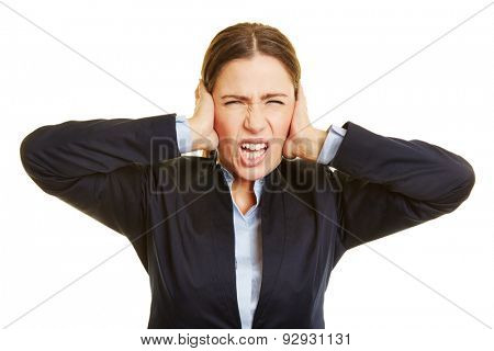 Angry business woman grimacing and covering her ears with her hands