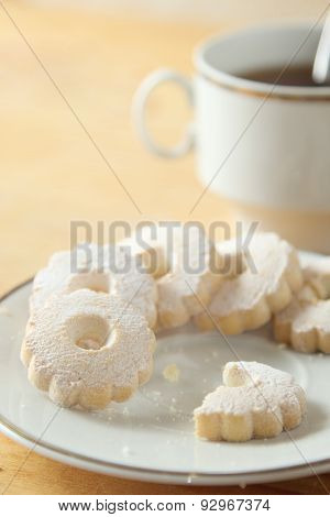 Nibbled Italian Canestrelli Biscuits Near A Cup Of Black Tea