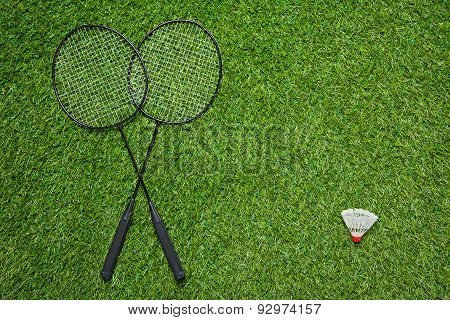 Crossed badminton rackets with white shuttlecock