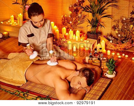 Man getting herbal ball massage treatments  in spa with burning candles.