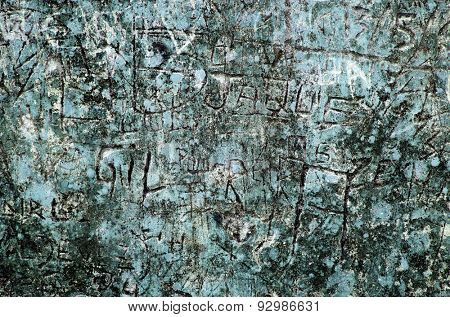 Grunge background of graffiti and sayings carved on a blue wall